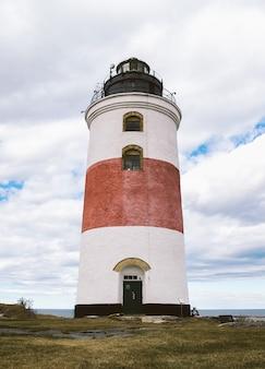 Красно-белый маяк у моря с облачным небом