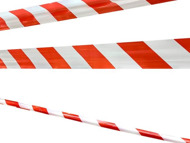 Красные и белые полосы заградительной ленты запрещают проход. барьерная лента на белом изоляте. барьер, запрещающий движение. предупреждающая лента. предупреждение об опасной опасной зоне: не входить. концепция запрета на въезд