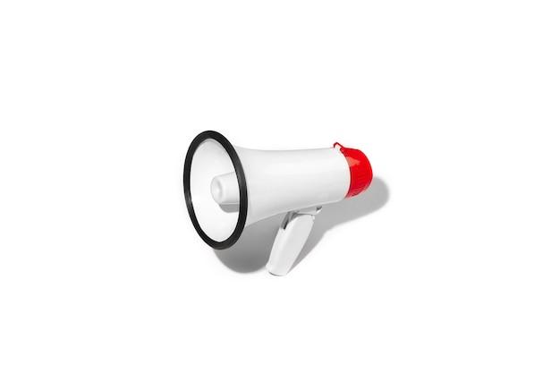 広告用のコピースペースと白いスタジオの背景に分離された赤と白のメガホン。公開会議、販売提案、叫び声、大音量のボイスメッセージ用の拡声器またはアドレススピーカー。
