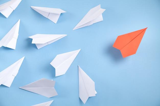 青の背景に赤と白の紙飛行機。リーダーシップ。チームワーク