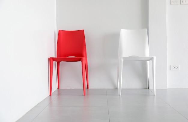 Красно-белые пластиковые стулья в углу белой комнаты.