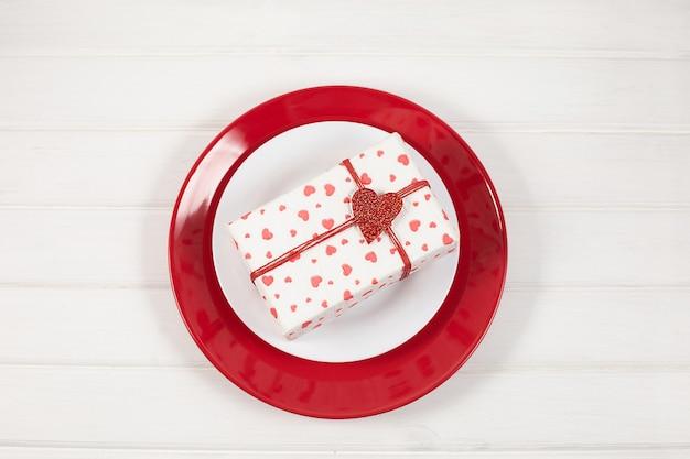 Красно-белая тарелка и подарок в коробке. концепция дня святого валентина.
