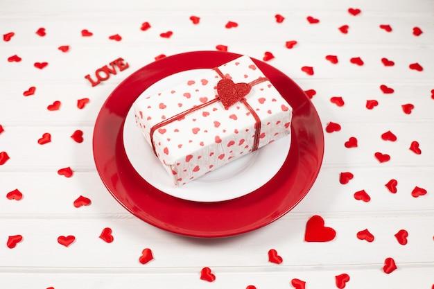Красно-белая тарелка, подарок в коробке и праздничный декор в форме сердца. концепция дня святого валентина.