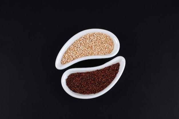 Красные и белые семена киноа в белых мисках на черном фоне