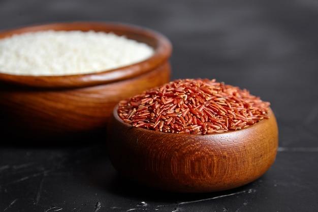Красный и белый рис в деревянных мисках на черном каменном столе. сухие сырые зерна