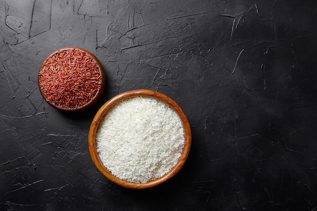 Красный и белый рис в деревянных мисках на черном каменном столе, вид сверху. сухие сырые зерна