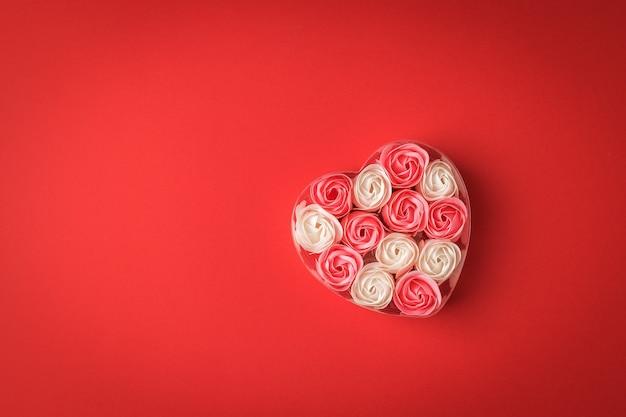 빨간색 바탕에 하트 모양의 상자에 빨간색과 흰색 장미 꽃 봉 오리. 사랑의 개념.