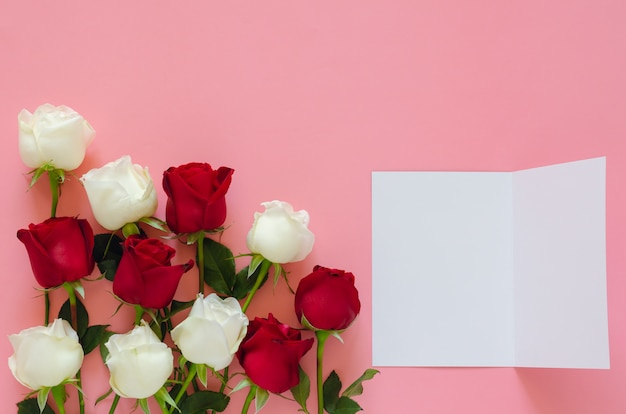 Красные и белые розы на розовом фоне с пустой белой карточкой на день святого валентина