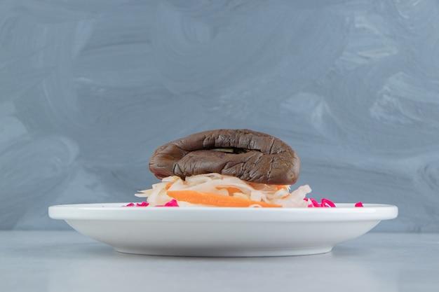 Красная и белая квашеная капуста с баклажанами на белой тарелке.