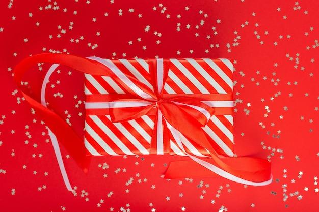 赤と白の縞模様のギフト ボックスにリボンと赤の背景にリボン、キラキラ銀色の星、フラット レイアウト、トップ ビュー
