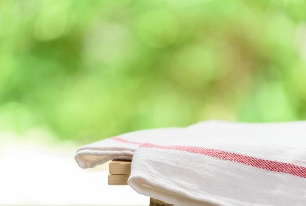 녹색 자연과 나무 테이블에 빨간색과 흰색 줄무늬 천으로 배경을 흐리게