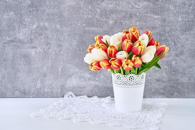 회색 배경에 흰색 꽃병에 빨간색과 흰색 튤립 꽃다발. 휴일 배경, 복사 공간.