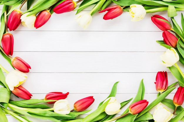 白い木製の背景に赤と白のチューリップ