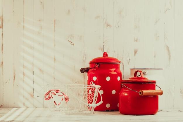 Красно-белая винтажная кухонная утварь на белом тальбе