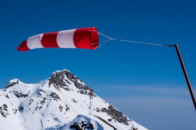 Красно-белый индикатор ветра сильно развивается в горах