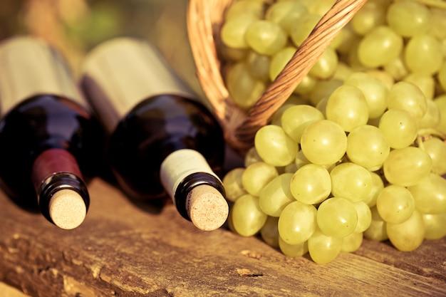 赤と白のワインボトルと木製のテーブルの上のバスケットにブドウの束。レトロなトーンの画像