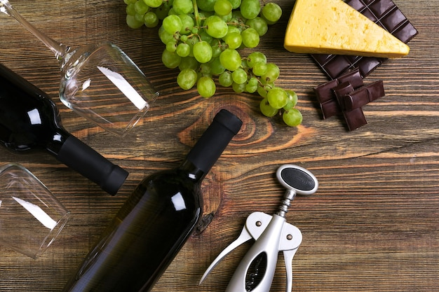 赤と白のワインボトル、ブドウ、チーズ、グラスを木製のテーブルの上に。コピースペースのある上面図。静物。フラットレイ