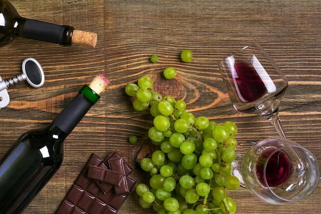 Красные и белые бутылки вина, виноградный шоколад и бокалы над деревянным столом с копией пространства