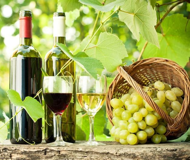 赤と白のワインボトル、グラス2杯、ブドウ園の古い木製のテーブルにブドウの房