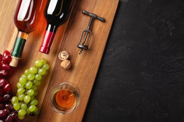 木の板と黒の背景にブドウ、ナッツ、コルク抜き、ワイングラスの束と赤と白のワインボトル。コピースペースのある上面図。
