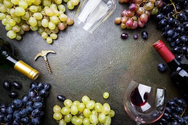 ダークストーンの上にガラス、ボトル、ブドウと赤と白のワイン