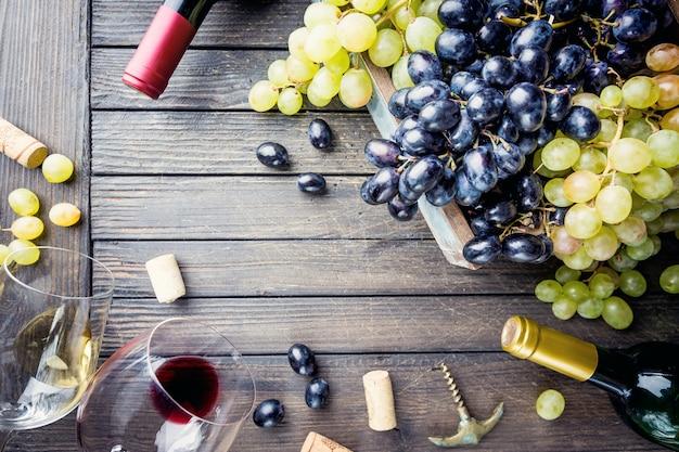 ガラス、ボトル、ブドウを木製に重ねた赤と白のワイン
