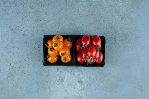 파란색에 빨간색과 노란색 체리 토마토입니다.