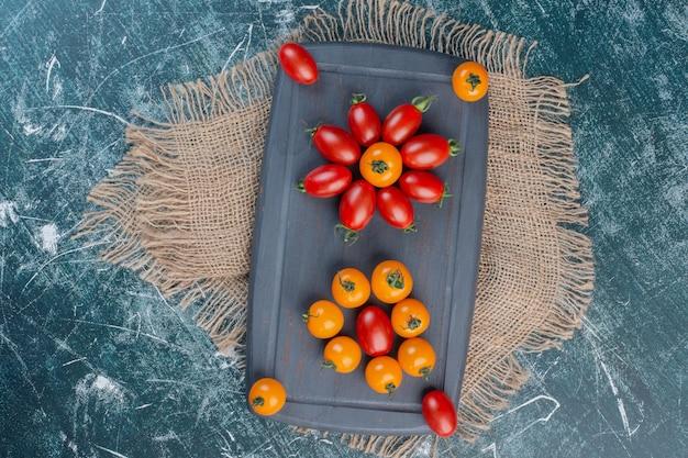 파란색 표면에 빨간색과 노란색 체리 토마토입니다.