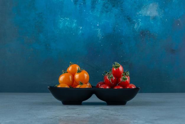 Красные и желтые помидоры черри на сером.