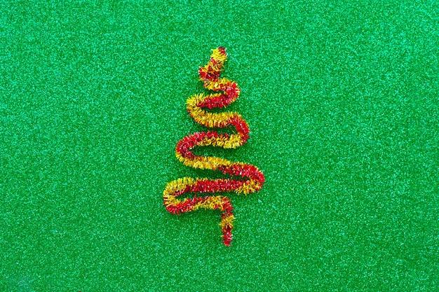 Красно-желтая фигурка елки на солнечном зеленом фоне. скопируйте пространство.
