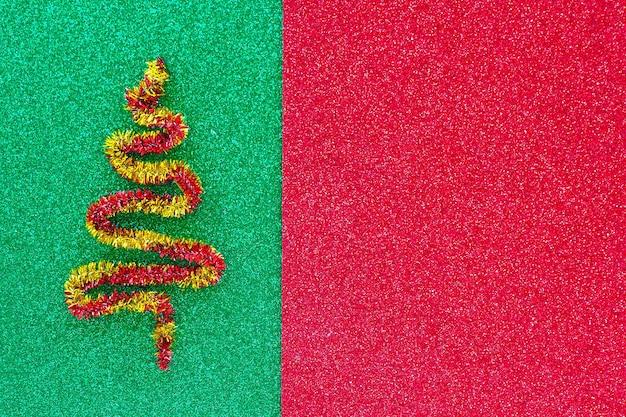 Красно-желтая фигурка елки на блестящем зелено - красном фоне. скопируйте пространство.