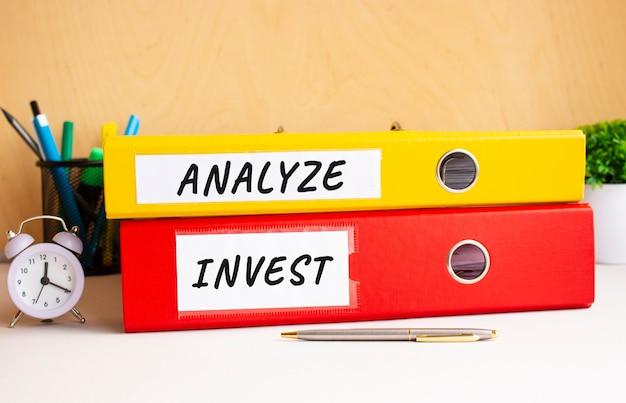 赤と黄色のフォルダーは、時計とペンの横にあるオフィスのテーブルにあります。 analyzeおよびinvestフォルダーの碑文。