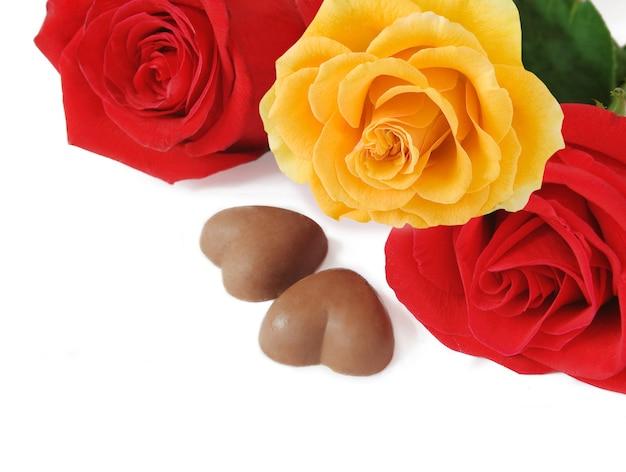 赤と黄色の新鮮なバラの花束、ハートのチョコレート菓子