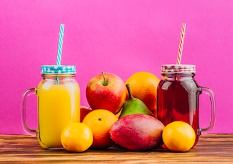 Red and yellow juice mason jars with drinking straws and fresh fruits against pink background