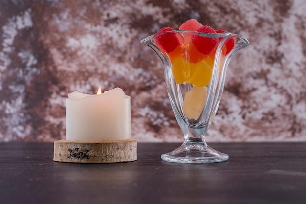 ガラスのカップに赤と黄色のマーマレード、大理石のスペースにキャンドル