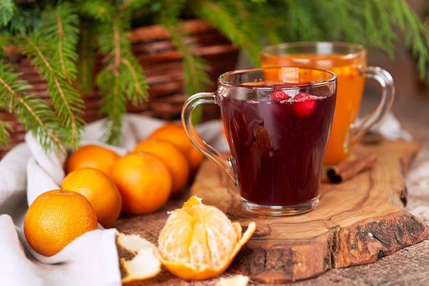 みかんのあるクリスマステーブルのガラスのマグカップに赤と黄色のグリューワイン。新年の静物をクローズアップ