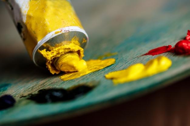 Красные и желтые масляные краски на палитре над деревянной стеной
