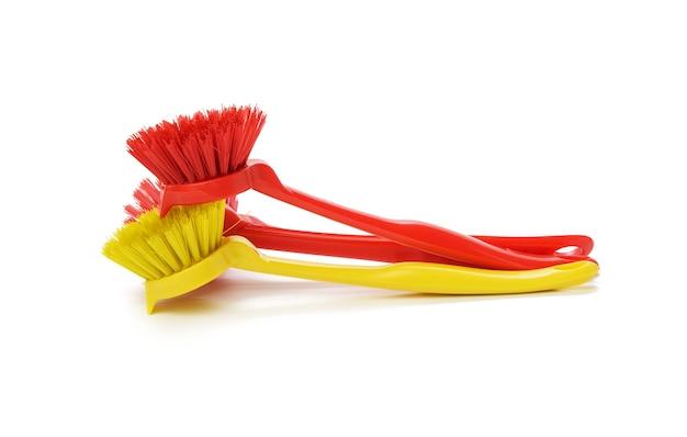 Красные и желтые пластиковые щетки с ручкой для очистки, изолированные на белой поверхности, крупным планом