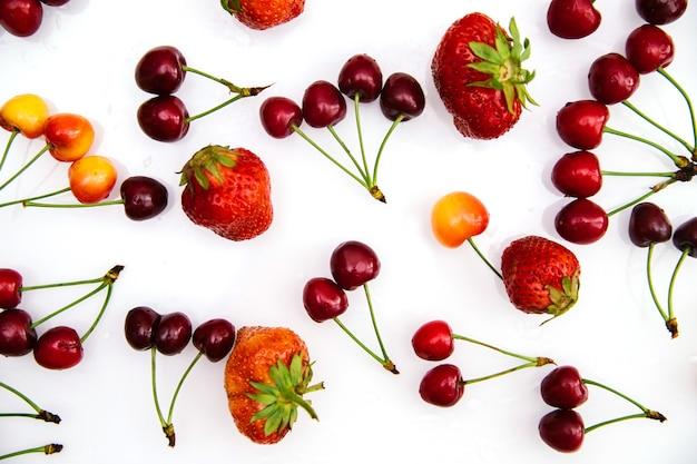 Красные и желтые спелые вишни и клубника. ягоды хаотично разбросаны по белому фону.