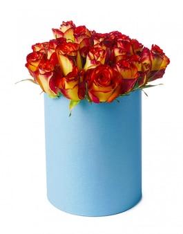 白で隔離される帽子ボックスに赤と黄色のバラ