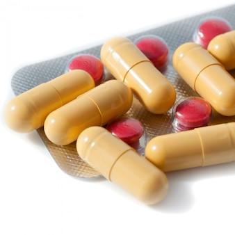Красные и желтые таблетки и волдыри разбросаны на белом фоне.