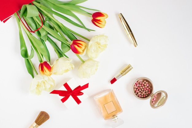 赤いギフトバッグに赤と黄色のチューリップ、化粧品、コピースペースのある白い背景のギフト。バレンタインデーや母の日のグリーティングカード。スタイリッシュなブロガーフラットレイ