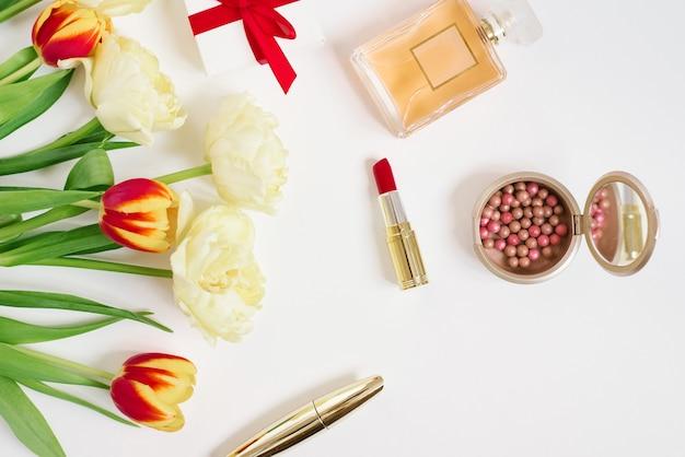 赤いギフトバッグに赤と黄色のチューリップ、化粧品、コピースペース付きの白い背景のギフト。