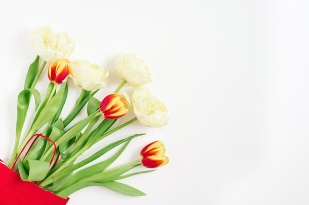 コピースペースと白い背景の上の赤いギフトバッグの赤と黄色のチューリップ。バレンタインデーまたは母の日グリーティングカード