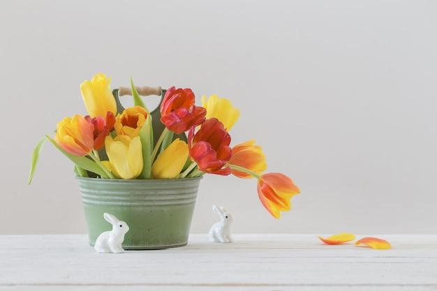 バケツと白い背景の上のセラミックウサギの赤と黄色のチューリップ