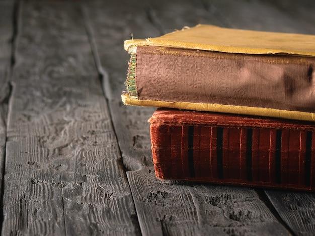 暗い木製のテーブルに赤と黄色のビンテージ本。過去の文学。