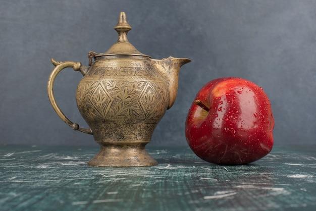 赤いリンゴと大理石のテーブルの上の古典的なティーポット。