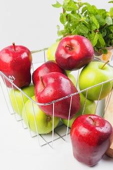 白い背景の上のバスケットに赤いリンゴと緑のリンゴ