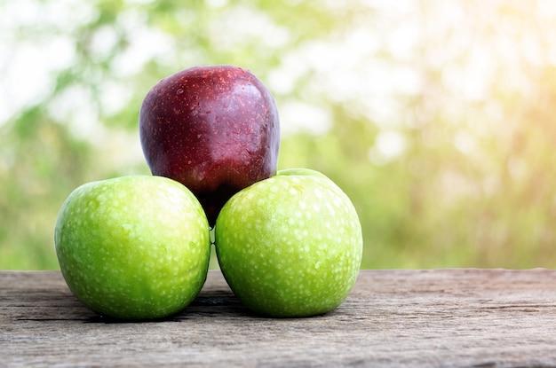 木製のテーブルに赤いリンゴと緑のリンゴ