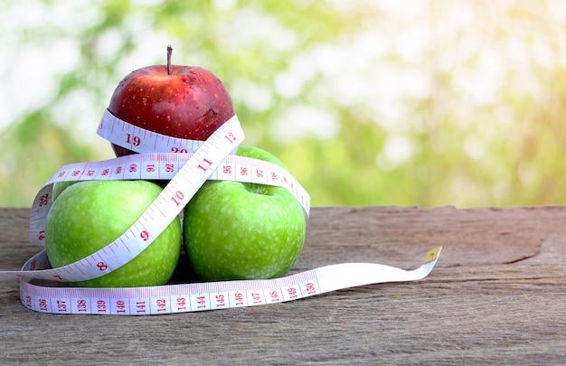木製のテーブルに巻尺と赤いリンゴと緑のリンゴ
